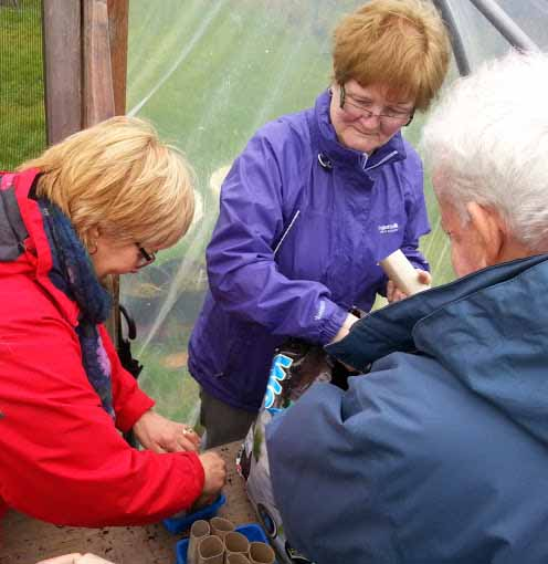 New gardeners learn about seeds guided by the more experienced